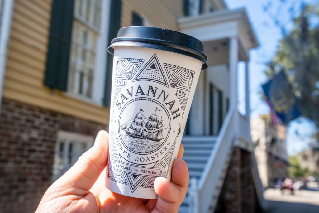 cup from savannah coffee roasters, one of the best coffee shops savannah ga, being held up in front of yellow building