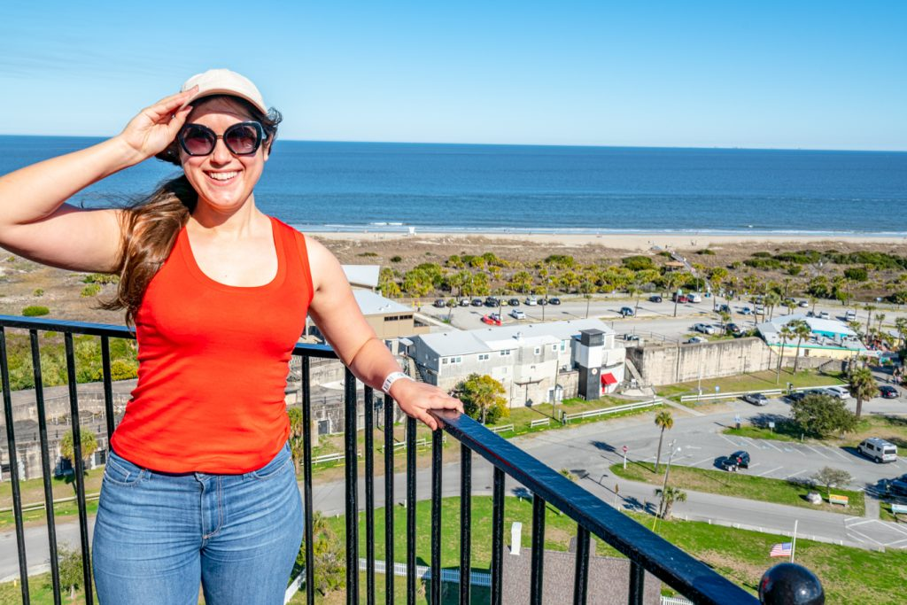 kate storm in an orange tanktop overlooking the beach of tybee island from the top of the tybee lighthouse, one of the best day trips from savannah ga