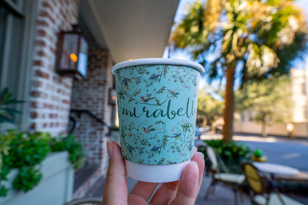 "colorful blue cup that says ""mirabelle"" being held outside of mirabelle cafe, one of the best savannah coffee shops"