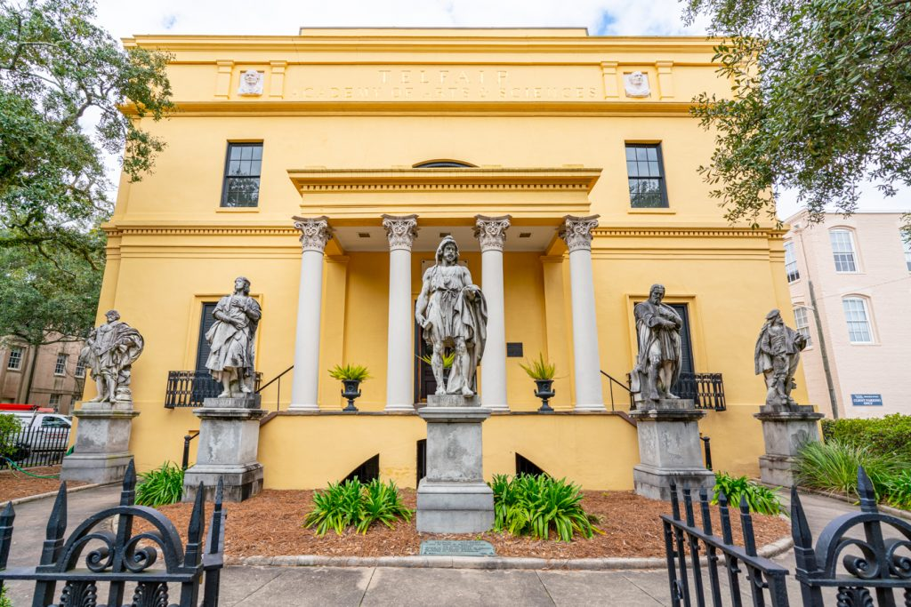 front facade of the telfair academy in savannah georgia, painted yellow with statues out front
