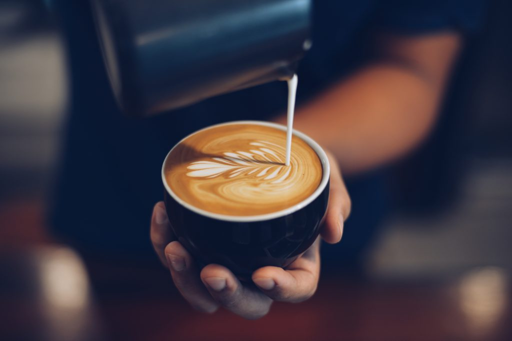 milk being poured into a latte by a barista
