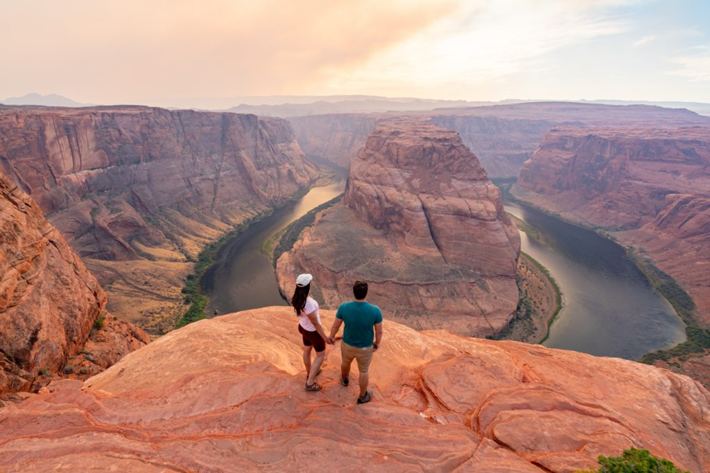 kate storm and jeremy storm holding hands overlooking horseshoe bend arizona