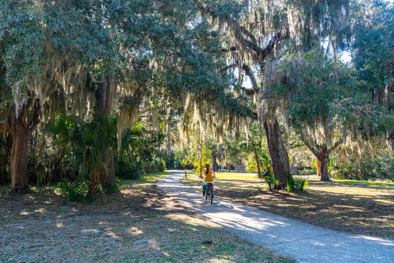 woman riding a bike through a path lined with spanish moss on jekyll island, one of the best day trips from savannah georgia