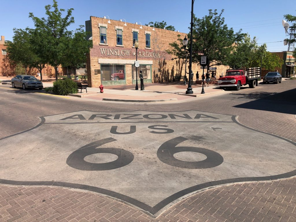 photo of standin on the corner park in winslow arizona with a route 66 sign in foreground painted on the ground