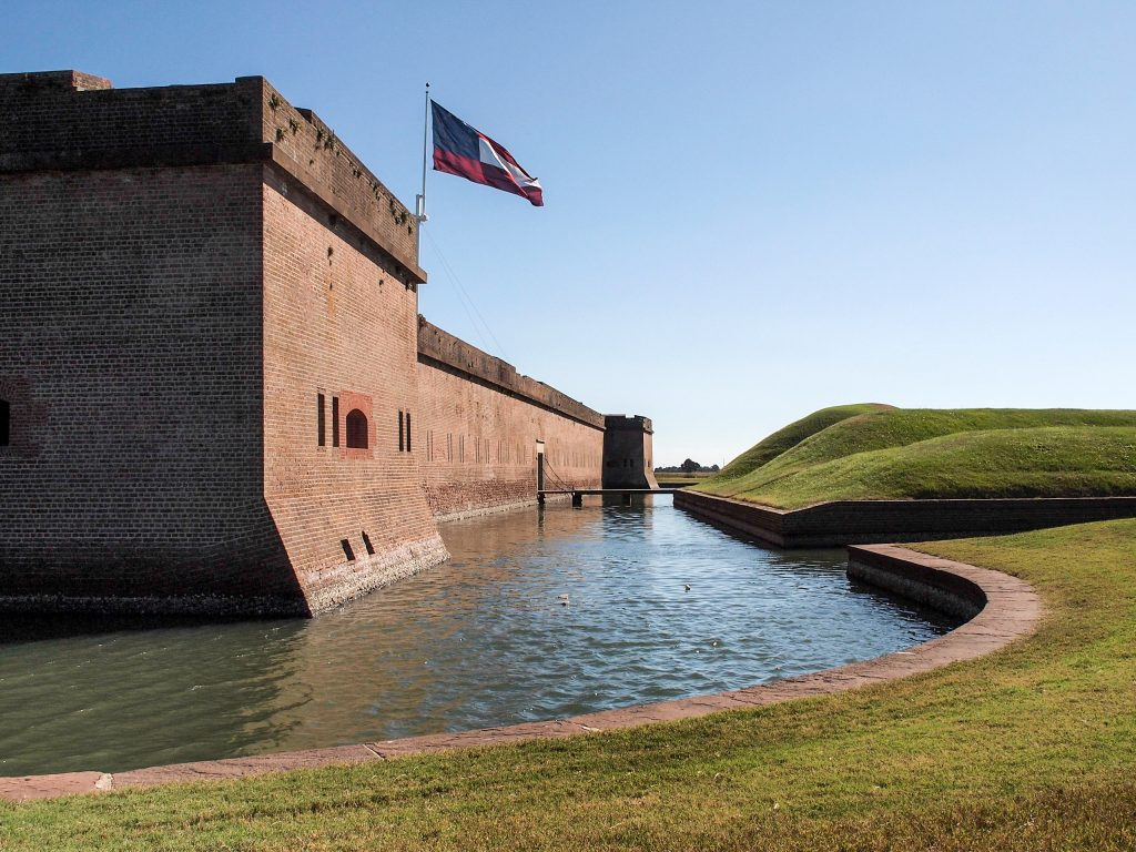 view of exterior walls of fort pulaski with moat in the center of the image