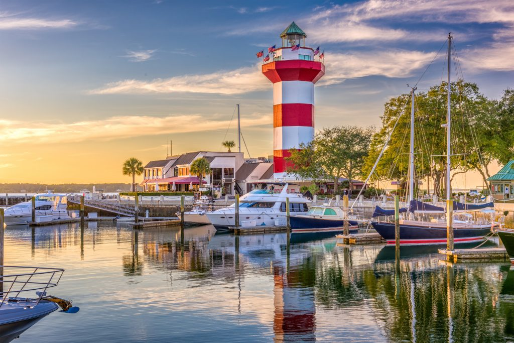 harbour town of hilton head island at sunset, with marina in the foreground and red and white striped lighthouse in the background