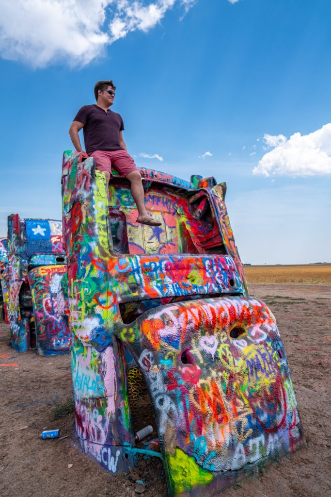 jeremy storm sitting on top of a car at cadillac ranch in amarillo