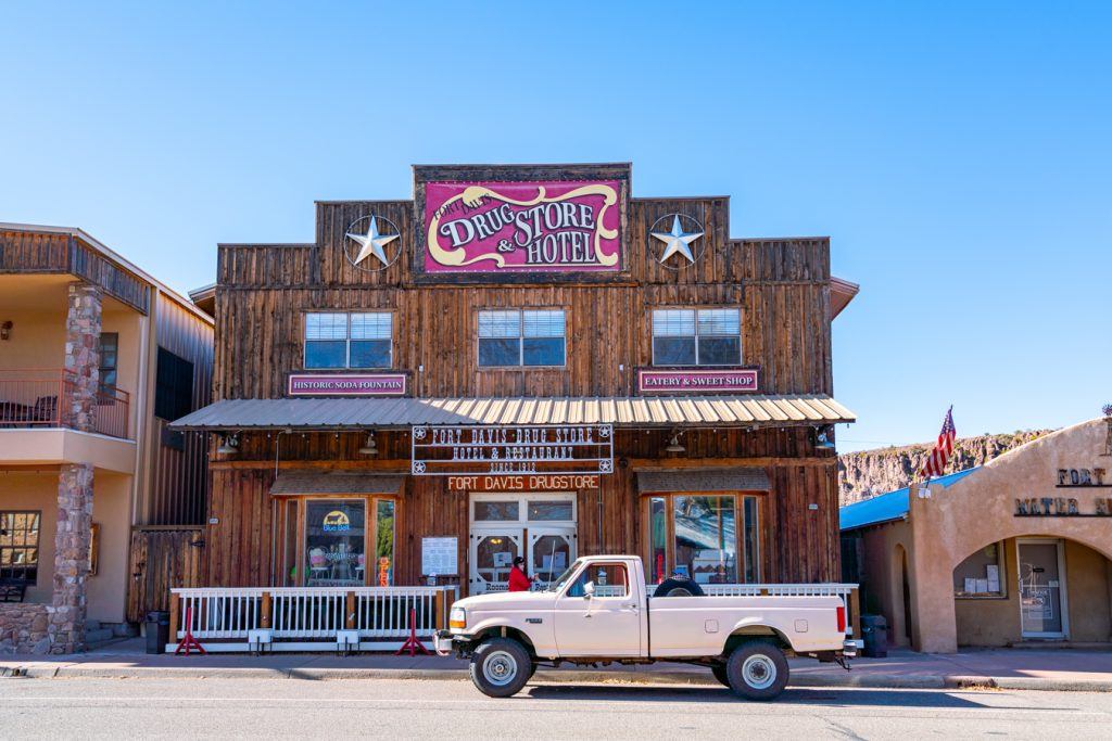 fort davis drugstore hotel in west texas with a pink truck parked in front of it, part of one of the best road trips in us southwest