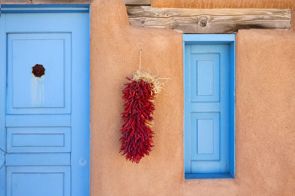dried chiles hanging from an adobe building with a blue door in santa fe new mexico