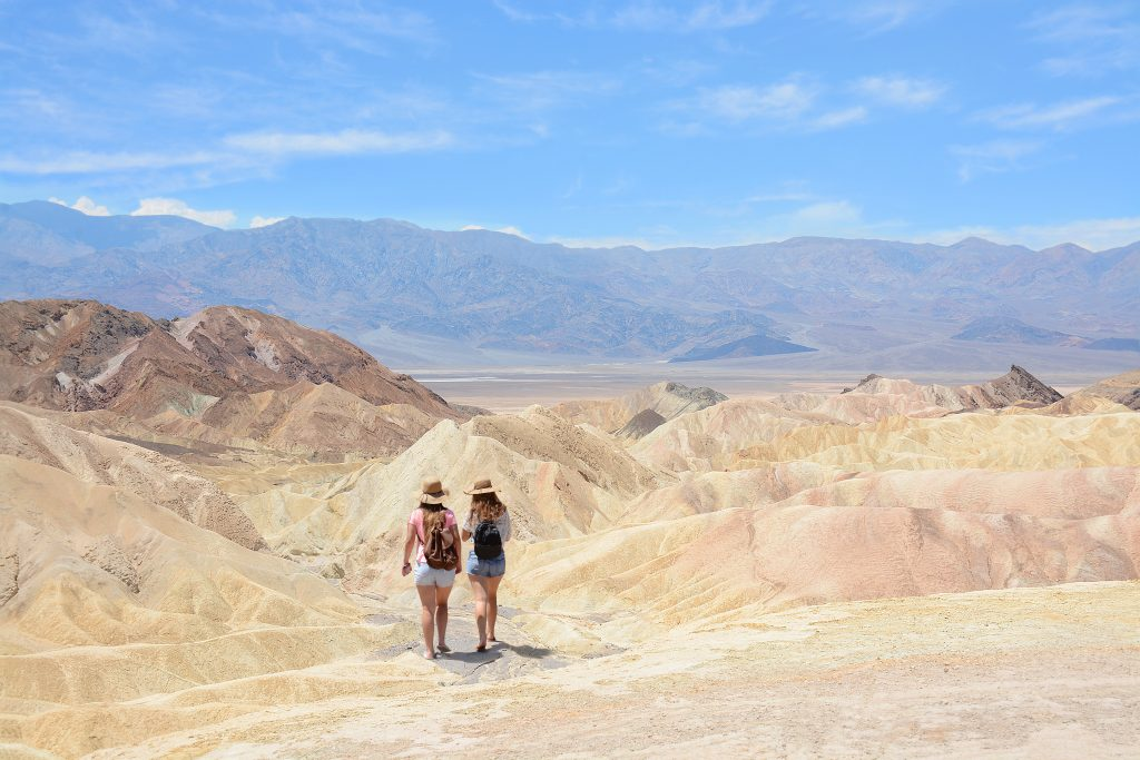 two women hiking through the desert of death valley, a popular us southwest road trip destinations