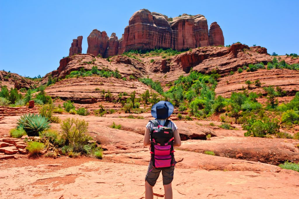 woman in a red backpack hiking in sedona on a southwest road trip of a lifetime