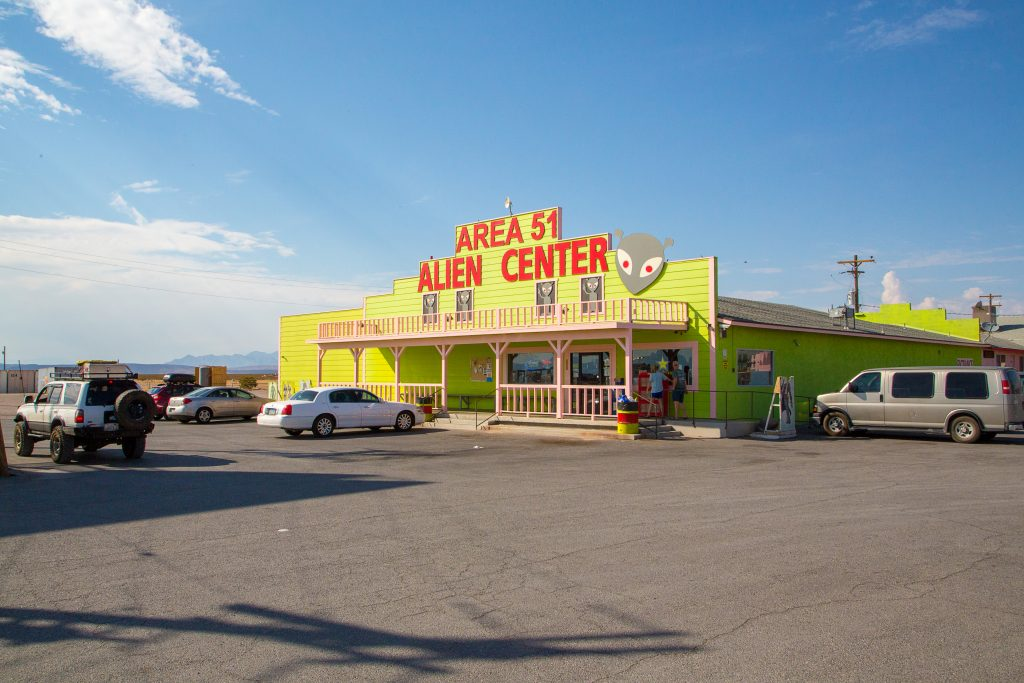 """bright yellow building as seen on a nevada southwestern us road trip that reads """"area 51 alien center"""" in red letters"""