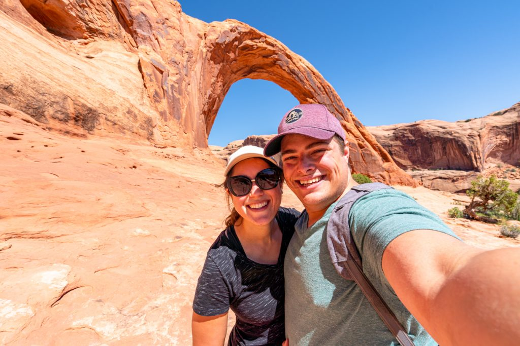 kate storm and jeremy storm taking a selfie in front of corona arch moab utah