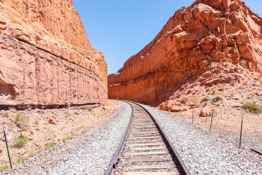 railroad tracks leading into a sandstone tunnel in utah