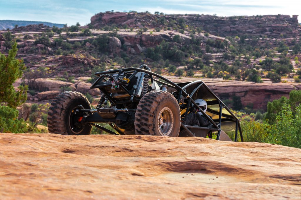 a black 4x4 climbing up a rock hill near moab. off-roading is one of the top moab activities