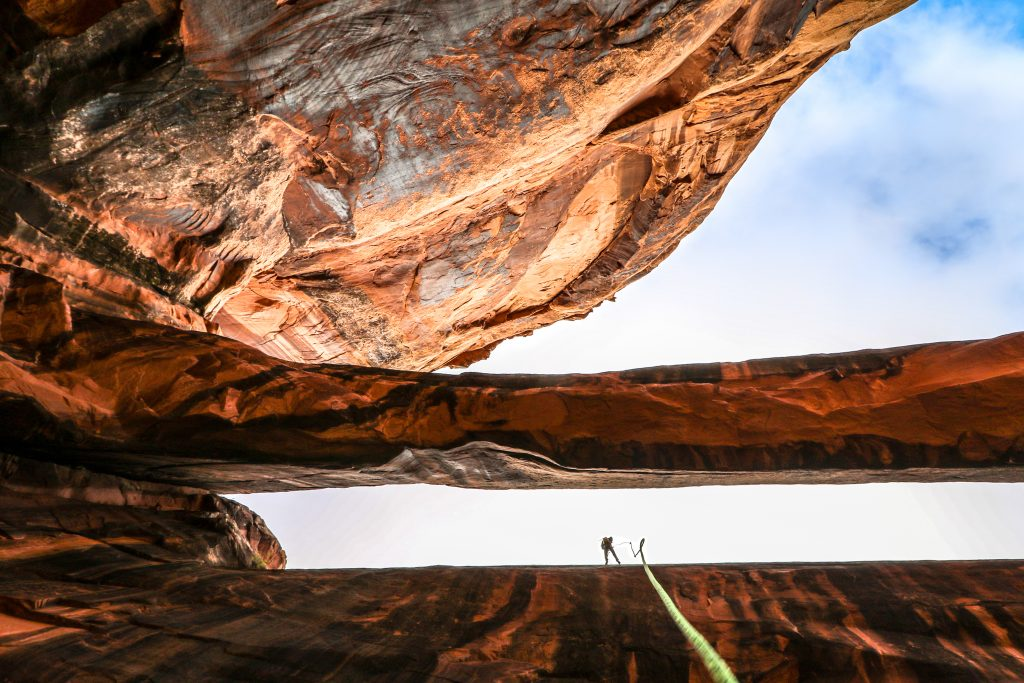 person preparing to rappell down a wall near moab, a green rope dangles in the foreground