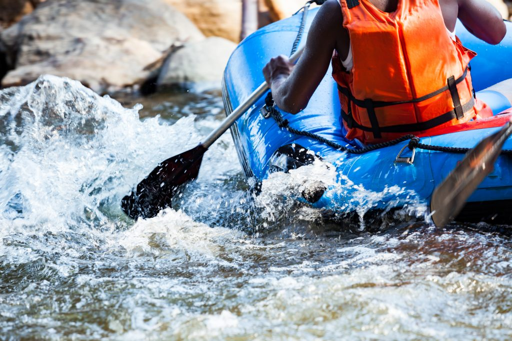 close up of a man paddling a blue white water raft through a rapid