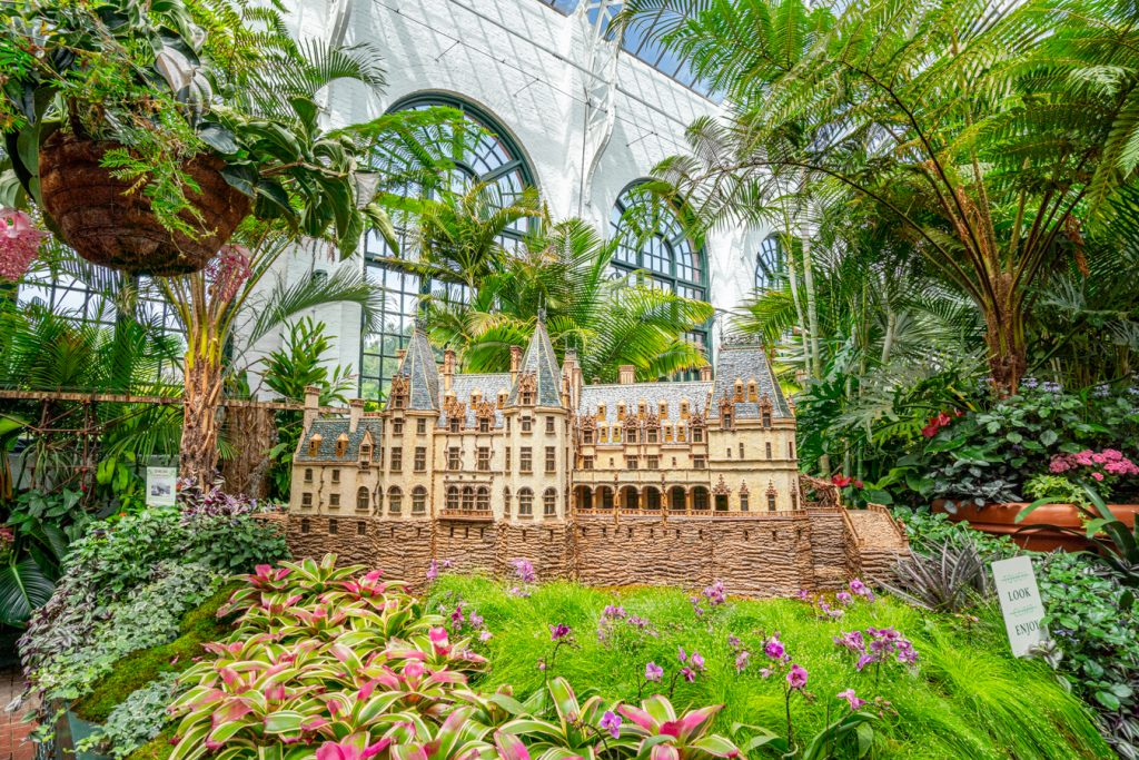 interior of biltmore conservatory with model biltmore house in the center