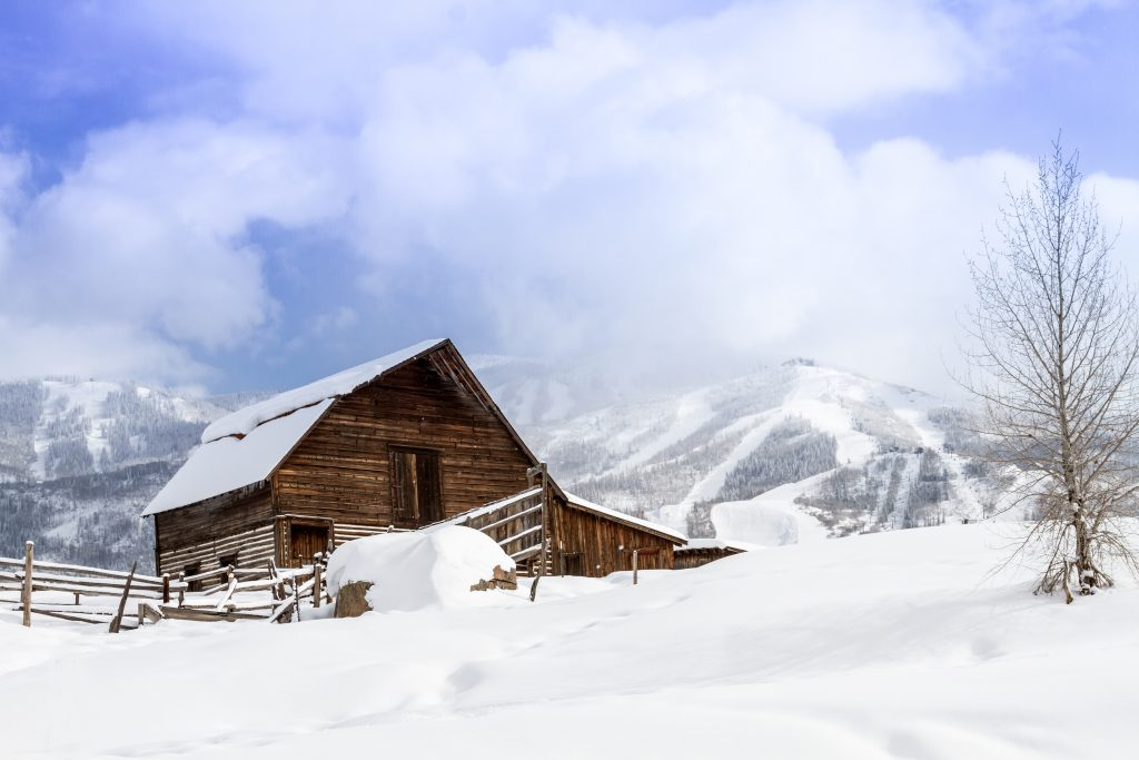 historic barn covered in snow in steamboat springs co, one of the best vacation spots in colorado