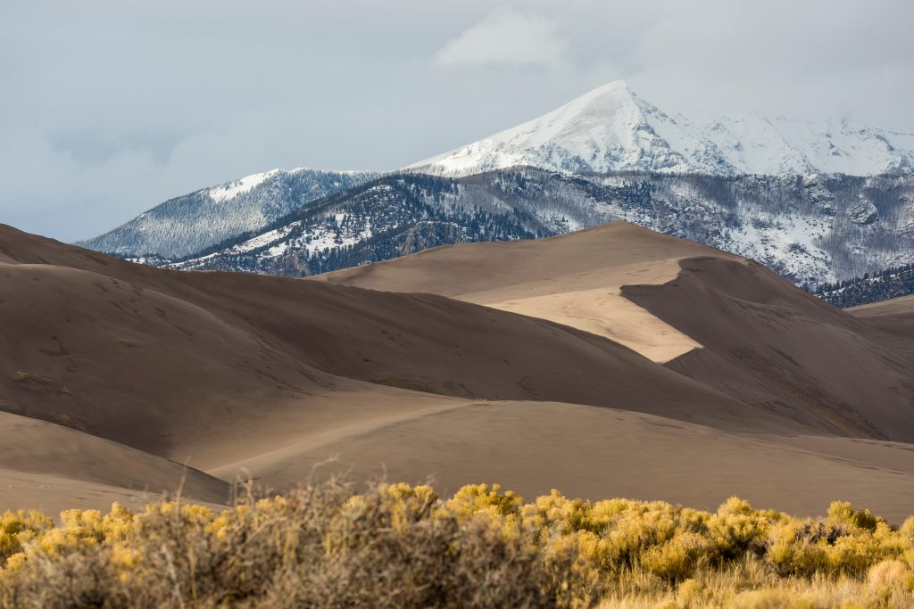 great sand dunes national park with snowcapped mountains in the background