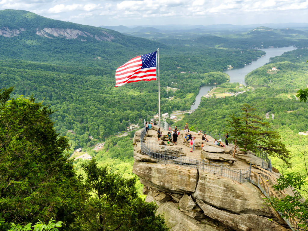 chimney rock nc with an american flag flying from it, one of the best things to see during a long weekend in asheville itinerary
