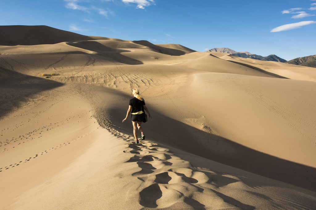 young woman hiking on a sand dune in great sand dunes national park, a bucket list colorado travel destinations