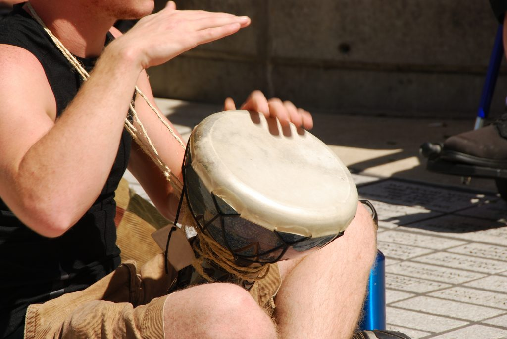 man playing a small drum in a drum circle