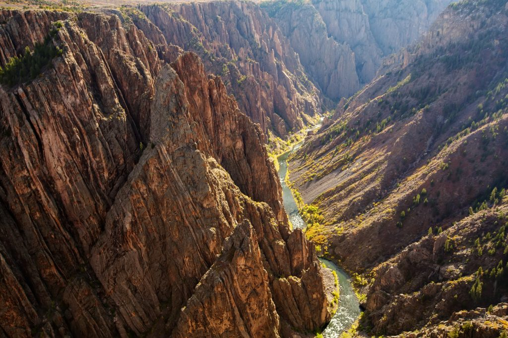 black canyon of the gunnison as seen from above with river to the right, one of the bucket list colorado places to visit