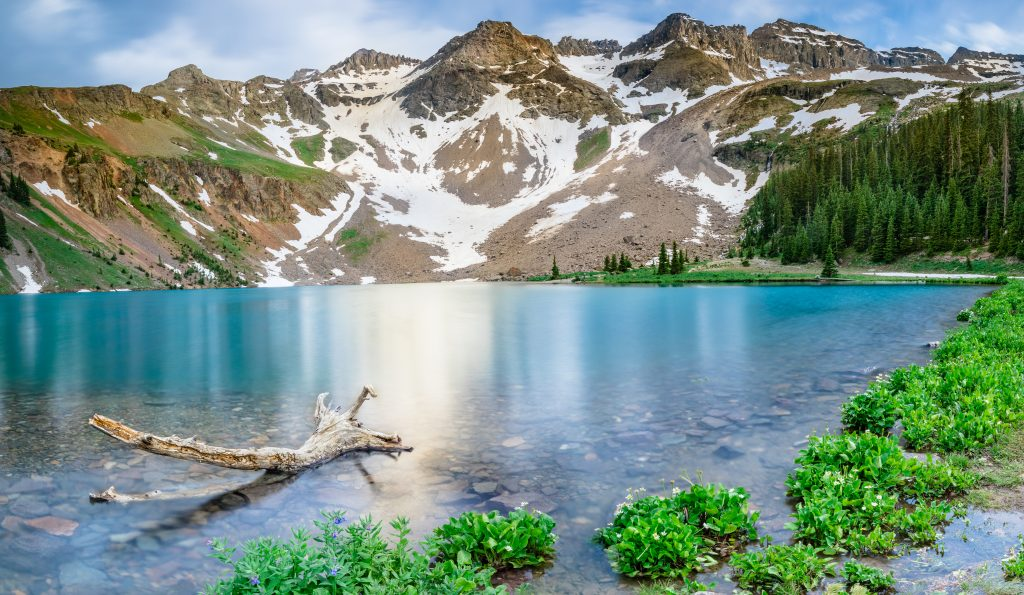 blue lake in colorado with mountains in the background, near one of the best colorado vacation spots telluride