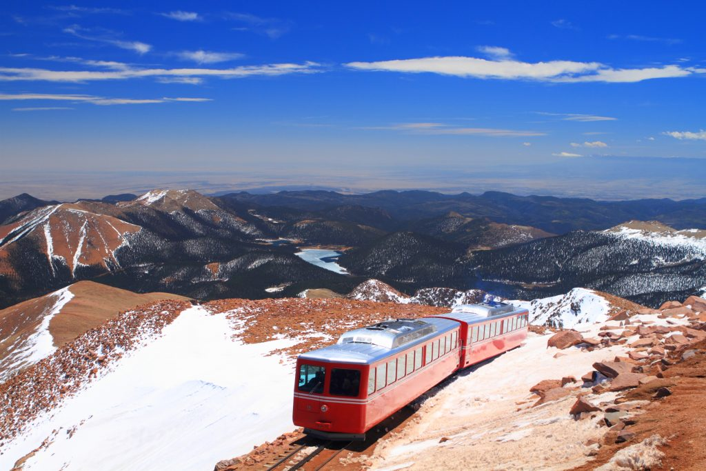 red pikes peak train climbing the mountain, one of the coolest places in colorado
