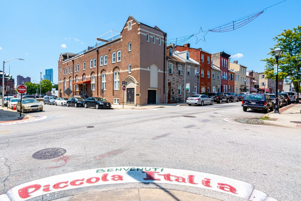 """view of little italy baltimore with """"piccola italia"""" painted on the street in the foreground"""