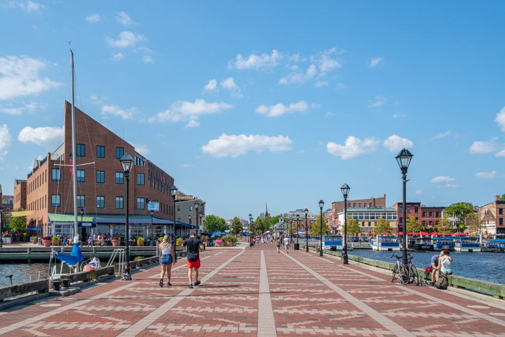 people walking along a paved pier in fells point, one of the best places to visit in baltimore in 2 days