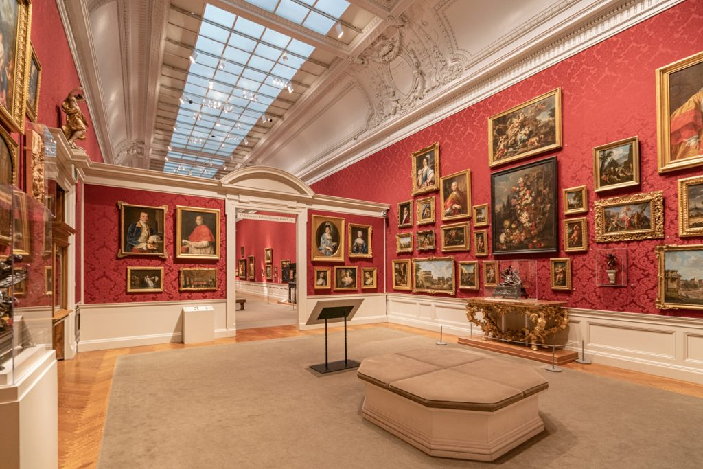 collection of renaissance paintings on display in a room painted red in walters art museum, as seen during a baltimore weekend trip