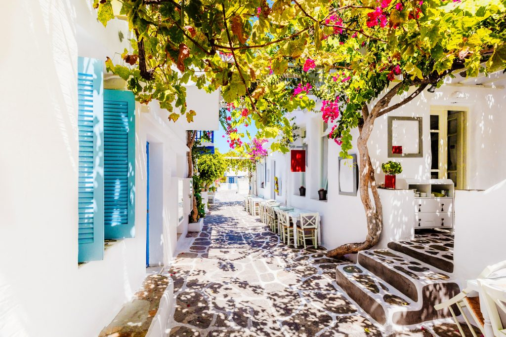 whitewashed buildings on a small street with pink flowers, a common sight when island hopping greece in 7 days
