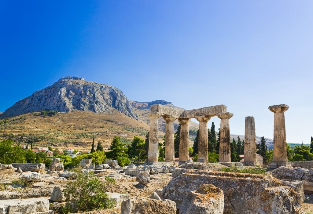 ruins of a temple in corinth greece with mountains in the background