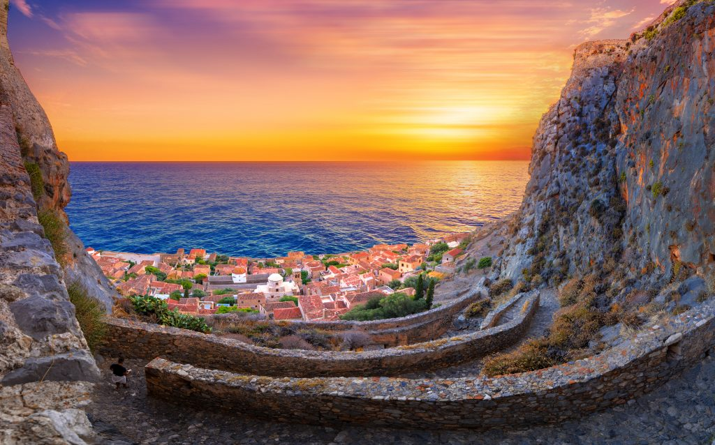 sunset over Monemvasia greece with winding stone road in the foreground
