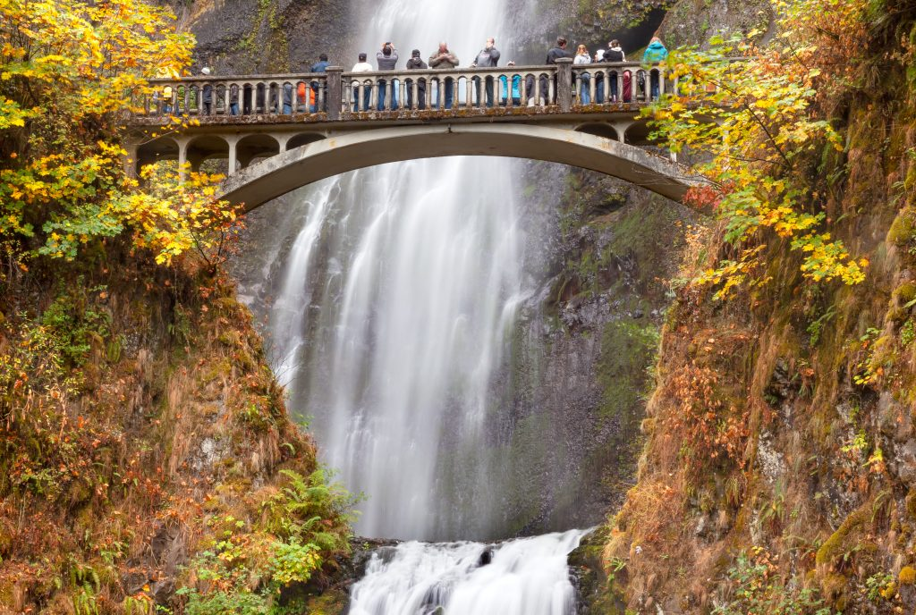 travelers admiring multnomah falls from historic bridge, best places to visit in usa in november