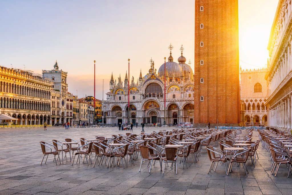 view of venice st marks square at dawn with cafe tables set out for the day