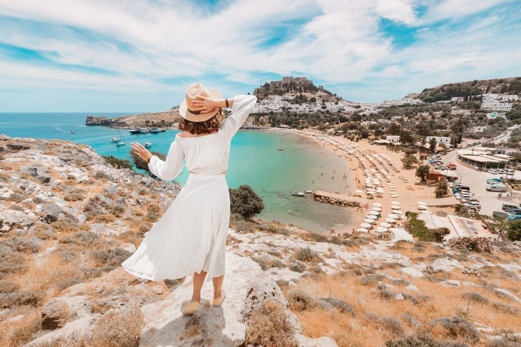 young woman in a white dress overlooking a beach in rhodes, a fun stop when exploring greece in 7 days island hopping