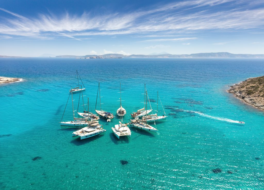 collection of sailboats gathered together in the waters of greece