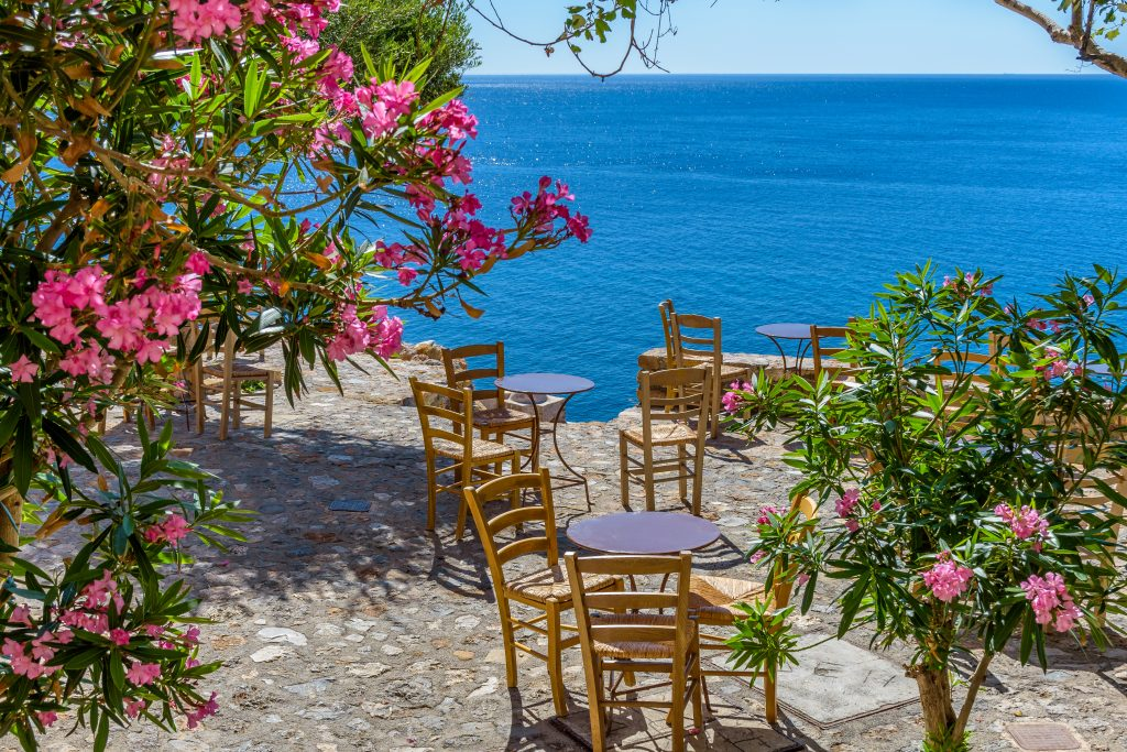 small tables overlooking the sea and surrounded by pink flowers as seen during an itinerary greece