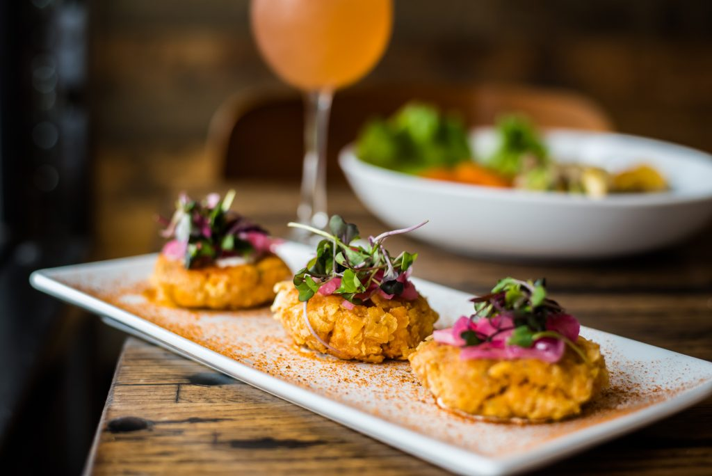 three crab cakes served on a white rectangular plate