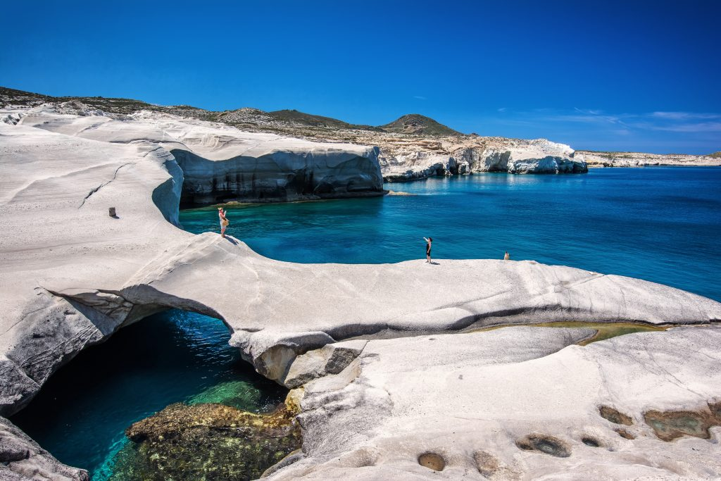 people walking over rock formations at Serakiniko Beach, one of the best places to visit in greece in 7 days itinerary