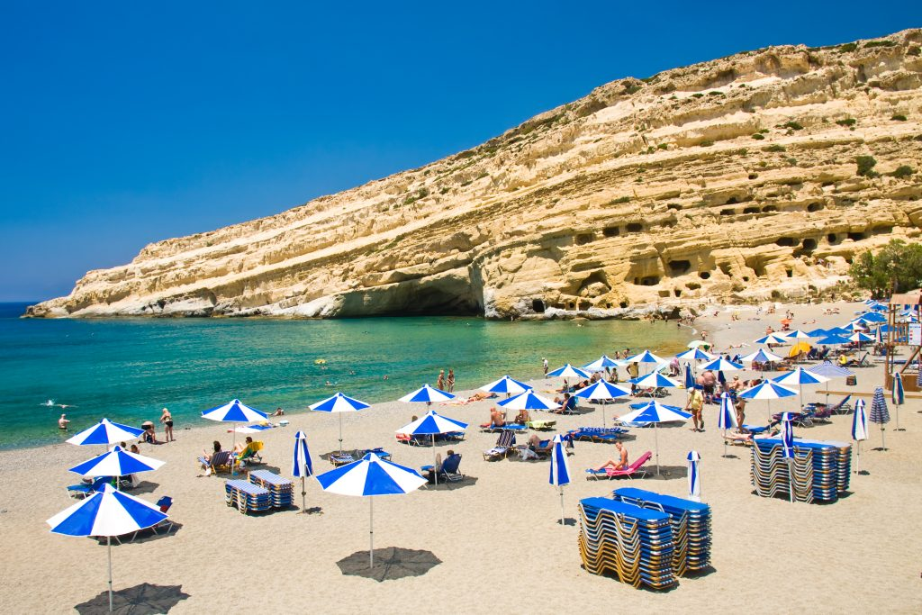 view of a crete beach with blue and white umbrellas on it
