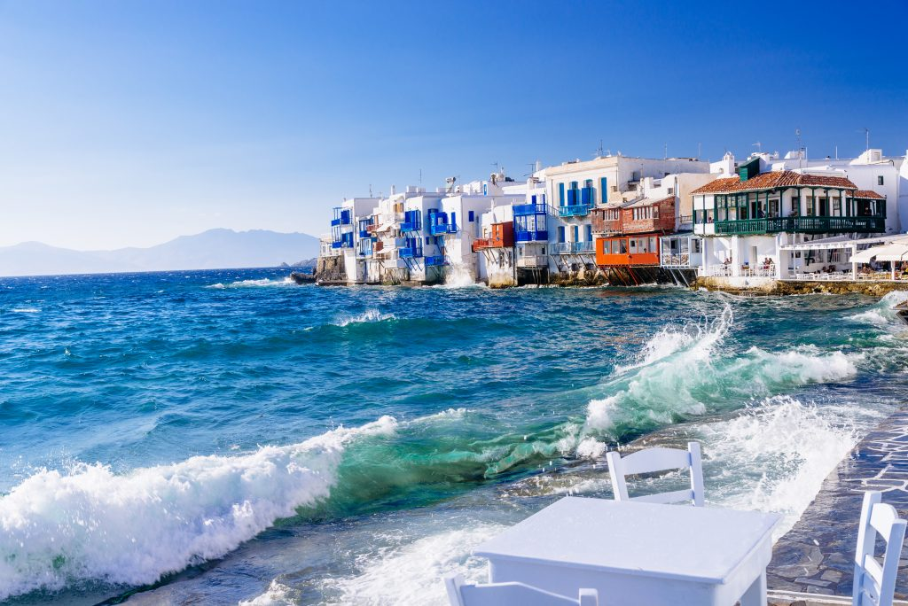 seaside view in mykonos greece with whitewashed buildings in the background, one of the best places to visit in greece island hopping itineraries