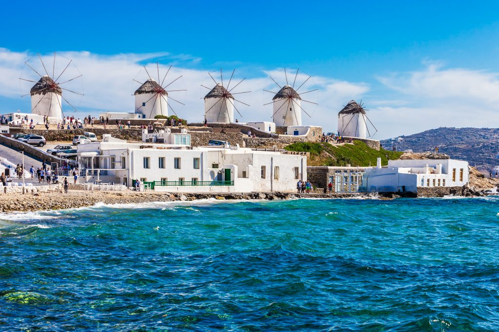 mykonos windmills as seen from the water, a popular stop on a greece island hopping itinerary