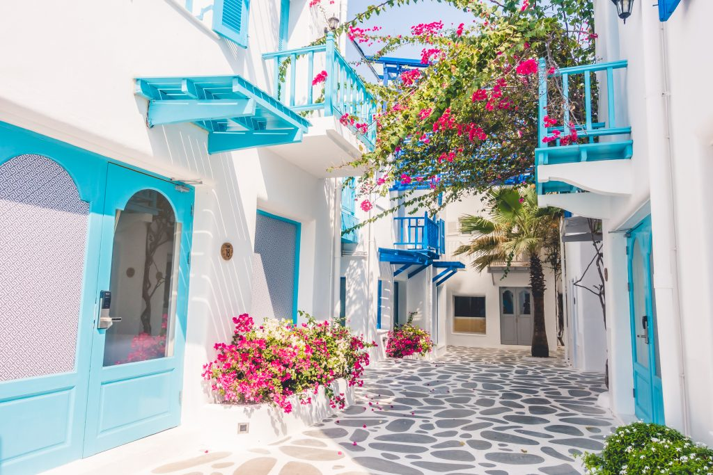 small street in a blue and white village greece with pink flowers