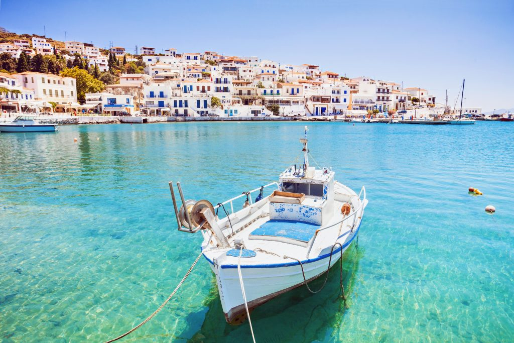 view of andros greece with the sea and a fishing boat in the foreground