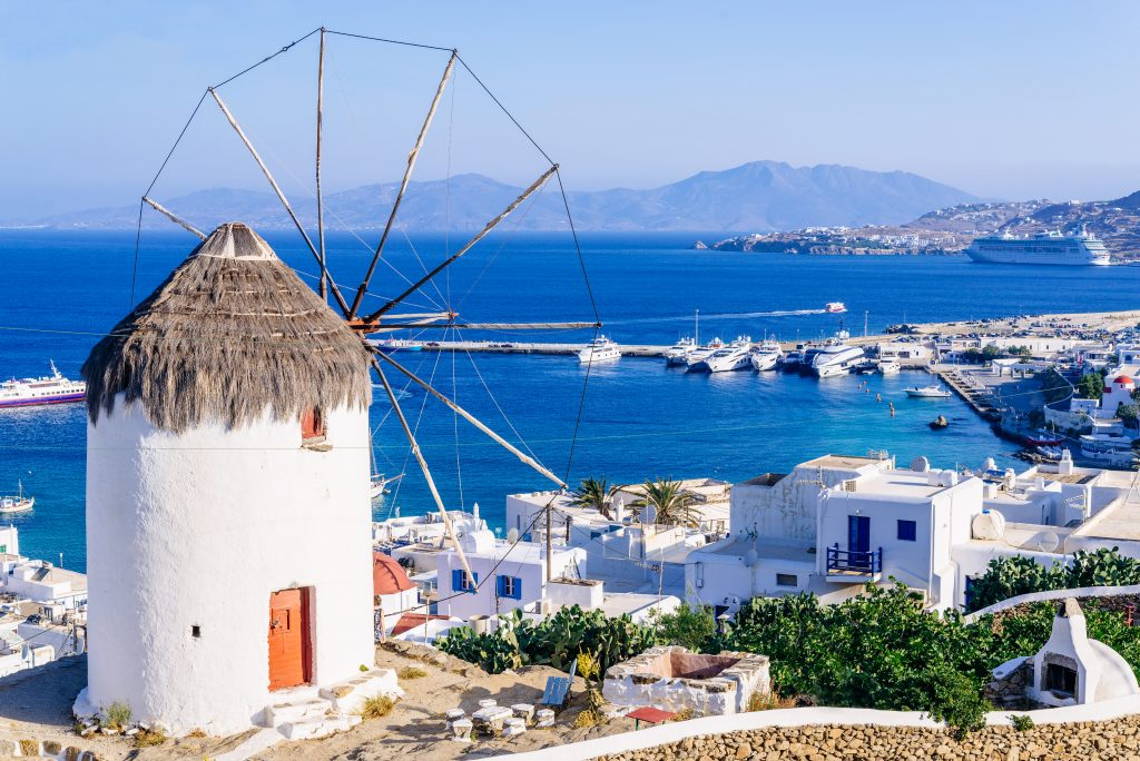 view of mykonos village and sea as seen from behind a windmill, which is prominent. mykonos is one of the most popular greek islands one week in greece