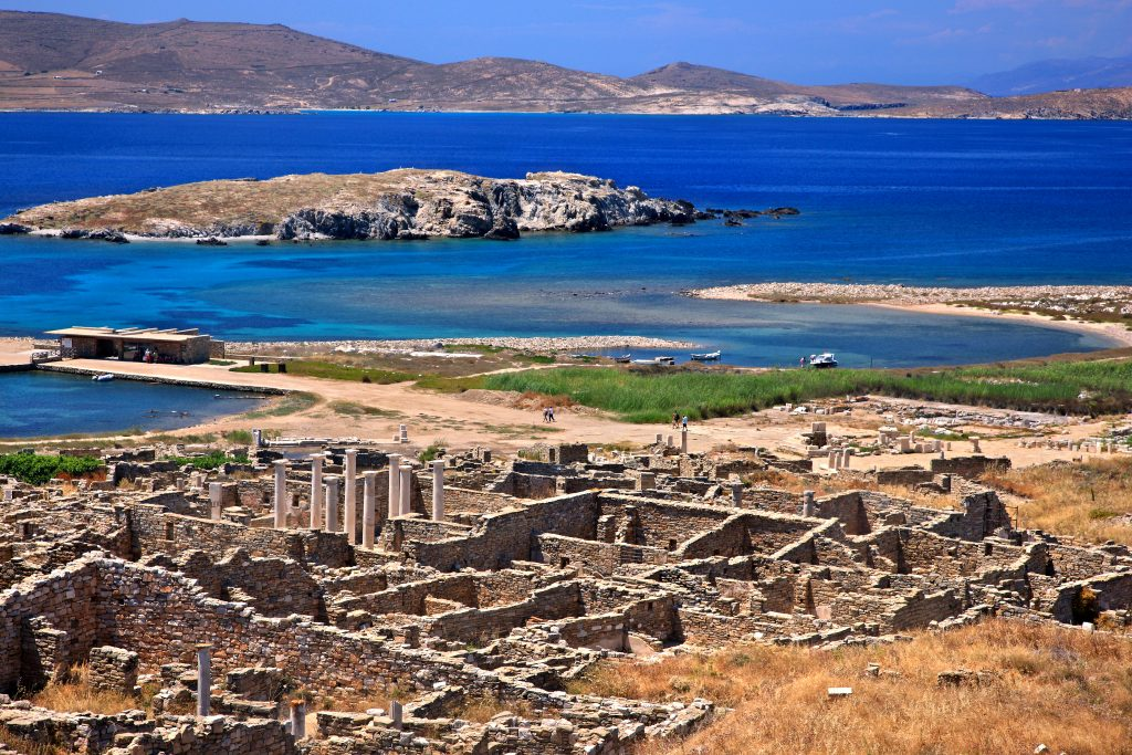 view of delos island greece from above with ruins in the foreground and sea in the background, one of the best stops on a itinerary for greece 7 days